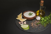 Tzatziki sauce with organic ingredients, spices and olive oil on dark board on black background