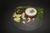 Tasty tzatziki sauce with spices, olive oil and ingredients on dark board on black background
