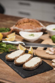 Bread with tzatziki sauce with fresh ingredients on wooden table