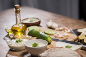 Delicious tzatziki sauce with ingredients and olive oil on wooden kitchen table