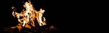 Karanlıkta kamp ateşinde yanan odunların panoramik görüntüsü