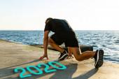 mladý běžec stojící na startovním místě na náspu u písmen roku 2020