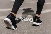 Fotografia cropped view of sportswoman on running track near 2020 lettering