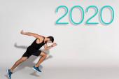boční pohled sportovce běžícího na bílém pozadí s nápisem 2020
