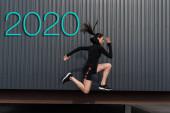 Fotografia side view of asian sportswoman running near wall with 2020 lettering