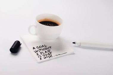 coffee cup on paper napkin with goal without plan just wish inscription, and felt pen on white table