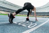 mladá sportovkyně stojící v start positing na běžecké trati v blízkosti 2020 písmo