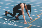 young sportswoman standing in start positing on running track near 2020 lettering