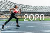 Fotografia young african american sportswoman running on stadium near 2020 lettering
