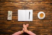oříznutý pohled na podnikatelku tření rukou při přípravě napsat novoroční usnesení v blízkosti dolarových bankovek a šálku kávy na dřevěném stole