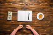 oříznutý pohled na podnikatelku držící pěsti při přípravě napsat novoroční usnesení v blízkosti dolarových bankovek a šálku kávy na dřevěném stole