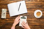 oříznutý pohled na podnikatelku pomocí kalkulačky v blízkosti prázdného notebooku, dolarových bankovek a šálku kávy na dřevěném stole