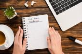 částečný pohled na ženské ruce v blízkosti notebooku s novoroční rezolucí nápisy v blízkosti notebooku, bezdrátových sluchátek, květináče a šálku kávy na dřevěném stole