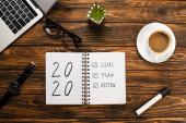 Fotografie Notizbuch mit 2020, Ziel, Plan, Aktionsschrift, Laptop, Kaffeetasse, Filzstift, Brille, Armbanduhr und Pflanze auf Holztisch