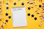 notebook s cíli do roku 2020 s prázdnými číslovanými body v blízkosti dekorativních, lesklých hvězd a hadovité na žlutém povrchu