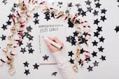oříznutý pohled na podnikatelku psaní 2020 cíle seznam v notebooku v blízkosti dekorativní hvězdy a hadovité na bílém stole