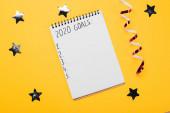 notebook s cílem 2020 nápis s prázdnými číslovanými body v blízkosti dekorativních, lesklých hvězd a hadovité na žlutém povrchu