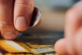 zblízka pohled na stříbrnou minci v ruce hazardního hráče v blízkosti poškrábaný los