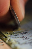 close up view of silver coin in hand of gambler scratching lottery card