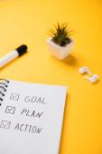 notebook s cílem, plánem, akčními slovy v blízkosti květináče, bezdrátovými sluchátky a plstěným perem na žlutém stole