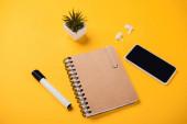 notebook poblíž smartphonu s prázdnou obrazovkou, bezdrátovými sluchátky, květináčem a plstěným perem na žlutém stole