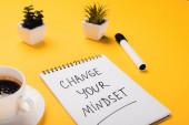 notebook megváltoztatásával a gondolkodásmód felirat közelében kávéscsésze, cserepes növények és filctoll sárga íróasztal