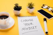 notebook változó gondolkodásmóddal felirat mellett kávéscsésze, cserepes növények, filctoll, okostelefon és szemüveg sárga asztalon