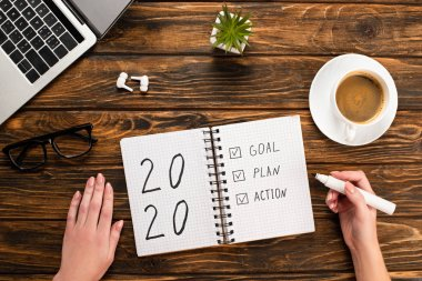 Cropped view of businesswoman holding felt-tip pen near notebook with 2020, goal, plan, action lettering near laptop, wireless earphones, coffee cup on wooden desk stock vector