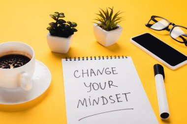 notebook with change your mindset inscription near coffee cup, potted plants, felt-tip pen, smartphone and glasses on yellow desk