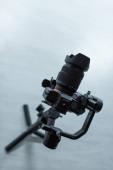 Photo black digital camera on tripod in studio