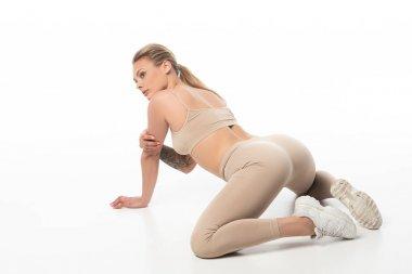 sexy blonde girl in beige leggings twerking isolated on white