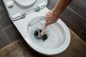 Photo cropped view of plumber using plunger in toilet bowl during flushing in modern restroom with grey tile