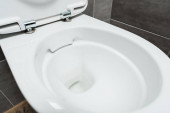 Photo close up view of clean ceramic clean toilet bowl in modern restroom with grey tile