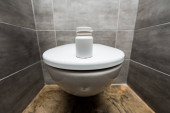 Photo container with pills on ceramic clean toilet bowl in modern restroom with grey tile
