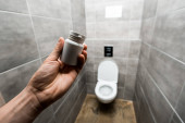 Fotografie abgeschnittene Ansicht eines Mannes, der Behälter mit Pillen in der Nähe von Keramik aufbewahrt, saubere Toilettenschüssel in einer modernen Toilette mit grauer Fliese
