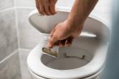 cropped view of man throwing away marijuana in toilet bowl