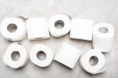 top view of rolls of toilet paper on grey textured surface