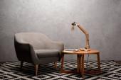 interiér obývacího pokoje s pohodlným šedým moderním křeslem u dřevěného stolu a lampou na koberci