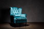elegant velour blue armchair near grey wall