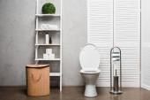 interiér moderní koupelny s WC mísou v blízkosti regálu s kosmetikou, ručníky, toaletním papírem, košem na prádlo a toaletním kartáčem