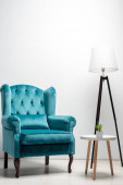 Fotografia elegant velour blue armchair with pillow near coffee table and floor lamp