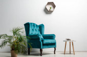 Fotografia interior of room with elegant velour blue armchair near green plant and coffee table near white wall