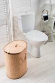 interiér bílé moderní koupelny s WC miskou v blízkosti skládací obrazovky, koš na prádlo, toaletní kartáč