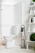 interiér bílé moderní koupelny s WC mísou v blízkosti skládací plátno, stojan a rostliny