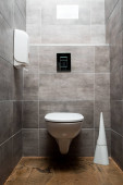 Photo interior of grey modern restroom with toilet bowl near toilet brush