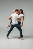 Tänzer in T-Shirts und Jeans tanzen Bachata auf grauem Hintergrund