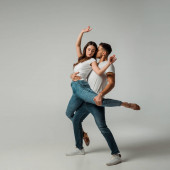 dancers in t-shirts and jeans dancing bachata on grey background