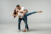 Tänzer in Jeans tanzen Bachata auf grauem Hintergrund
