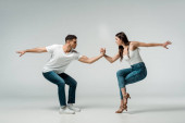 side view of dancers in denim jeans dancing bachata on grey background