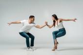 boční pohled na tanečníky v džínách tanec bachata na šedém pozadí